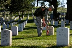 U.S. Army Spc. Ian Nickerson places an American flag on a grave at Arlington National Cemetery for Memorial Day, in Arlington, Va., Thursday, May 21, 2009. (AP Photo/Jacquelyn Martin)